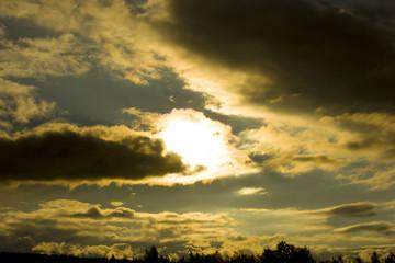 the sun shines through dark clouds at sunset