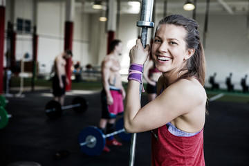 Portrait of smiling woman with barbell pole in gym