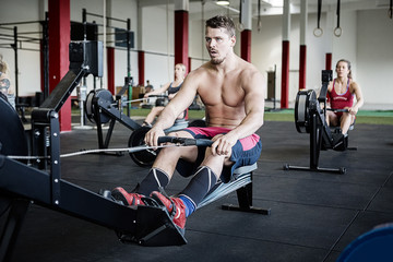 Shirtless Man Using Rowing Machine In Gymnasium