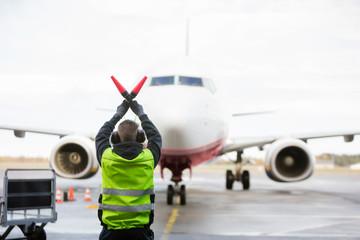 Ground Worker Signaling To Airplane On Runway