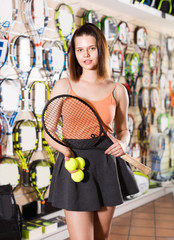Female standing in sporting goods store with balls and racket