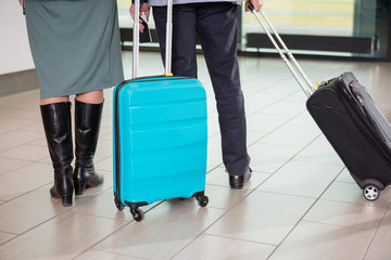 Senior Business Couple With Trolley Bags Walking At Airport