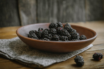 The blackberry in a ceramic bowl lies on a wooden table.