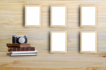 photo frames on wooden wall and camera,retro book on a wood desk with Mock up and copy space.