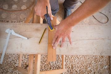 Carpenter using clamp tool and preparing raw wood.