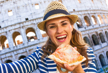 tourist woman in Rome, Italy with pizza slice taking selfie