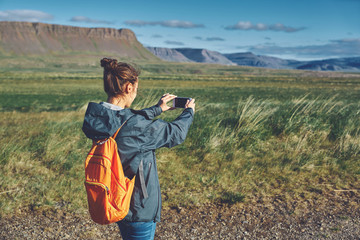Girl in warm clothing photographing a beautiful landscape with background of mountains of Iceland.