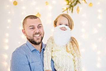 Christmas and new year 2018. Dad and daughter try on the beard of Santa Claus and they are very happy. Christmas lights are on the wall.