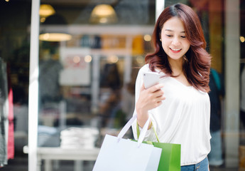 Young woman at the street with shopping bags and using mobile phone