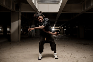 Dancing afro american man in black clothes