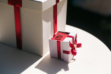 Engagement Diamond ring in a white box with red ribbon and present