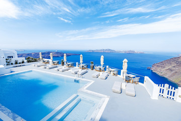 Swimming pool  with beautiful view on Aegean sea, Santorini, Greece at hot sunny summer day.