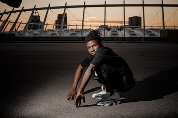 Outdoor portrait of squatting young afro american guy
