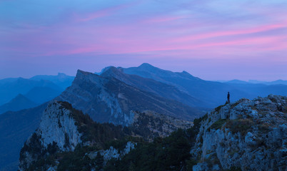 Fotomurales - Hiker looking at the mountains and the pink sky during dusk. Vercors, France.