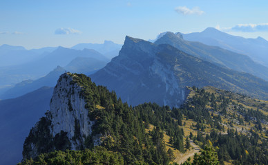 Fotomurales - Hiker standing on top of a small, distant peak in the mountains. Vercos, France.
