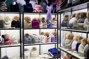 Winter colorful hats with fur pompom in shop