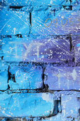 The texture of the old brick wall, painted in blue and purple colors with carelessly spaced white drops and splashes that visualize the stars in outer space