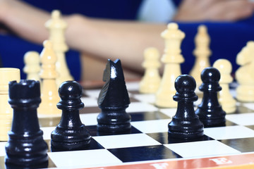 Wooden chess pieces stand on a chessboard against the background of a woman's fuzzy sitting figure in the room.