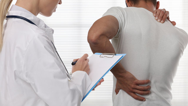 Female Doctor and male patient suffering from back pain during medical exam.