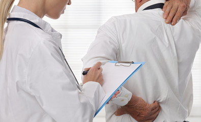 Female Doctor and senior male patient suffering from back pain during medical exam.