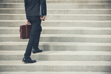 Businessman wearing black suit holding bag and folder walking up the stairs