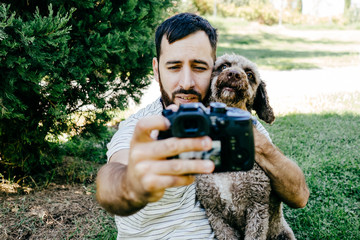 .Young man enjoying a sunny day in the park with his brown dog. They are taking a picture together with the camera. Lifestyle