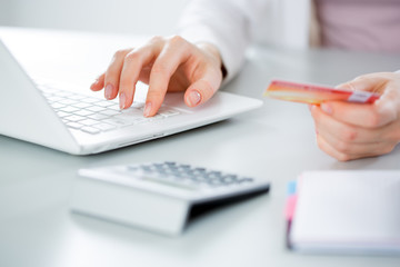 Business woman holding credit card and using laptop.