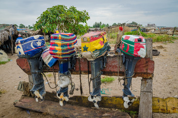 Colorful lined up fishing boat engines with artistic covers on wooden stand, The Gambia, West Africa