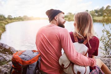 Couple sitting at lake side embracing