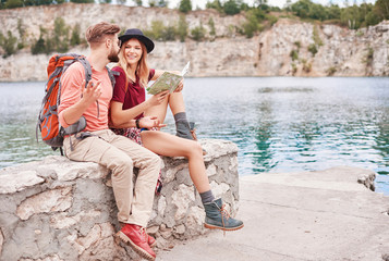 Couple sitting on wall by water looking at map, Krakow, Malopolskie, Poland, Europe