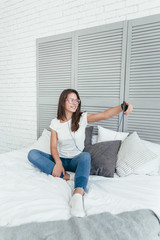 Young pretty woman sitting on the bed and does selfie with a phone