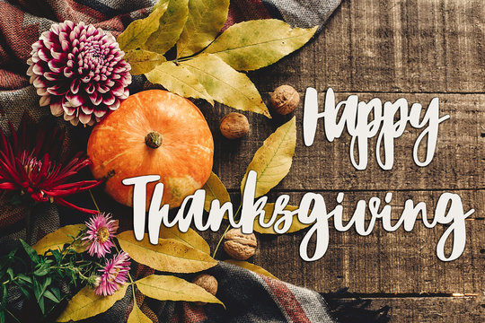 happy thanksgiving text sign on autumn pumpkin with leaves and walnuts and dahlias on stylish scarf top view, space for text. seasonal greetings, fall holidays. flat lay. harvest time. cozy mood