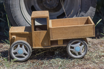 Wooden toy truck on the background of the wheel of a large truck.