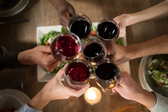 Friends toasting red wine in restaurant