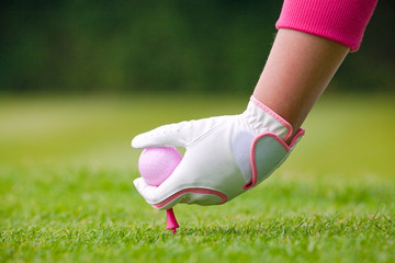 Lady golfer placing pink ball and tee into the ground.