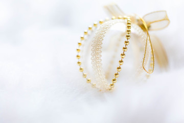 Gold Christmas baubles on white fur. Festive winter concept.