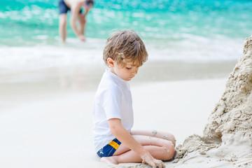 Little kid boy building sand castle on tropical beach