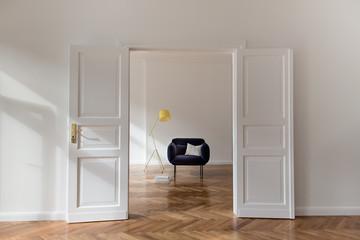 Sonnendurchflutete Altbauwohnung mit Flügeltür und gemütlichem Sessel in