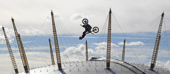 Action sports performer Pastrana somersaults on his motorbike as he jumps between two barges on the River Thames with the O2 Arena sports venue seen behind, in London, Britain