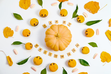 Happy Halloween with fake pumpkins and tangerines with painted scary faces candy jaw and autumn leaves on White Background