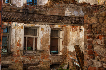 Old abandoned red brick house ruin, damaged by earthquake, war or other natural disaster, demolished decay debris