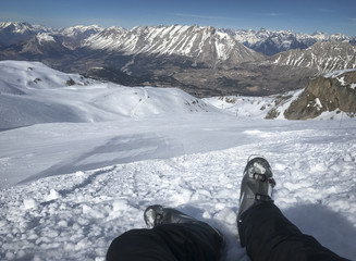 Skier resting in the snow with view on ski slope and Alps