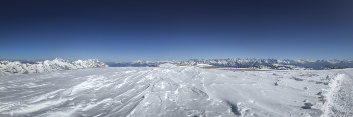 Panorama winter mountain scenery wind shaped snow foreground and blue sky