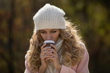 Woman in scarf and hat drinking hot tea in autumn day at park, blurred background