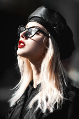 Fashion woman in black leather cap, trendy glasses and red lips. Stylish look in fashion coat outside. Autumn look.