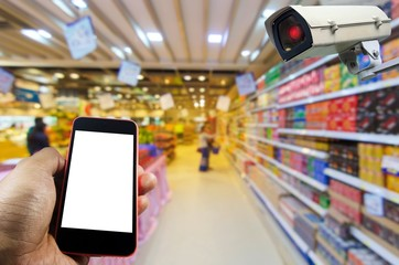 hand using smart phone and CCTV security indoor camera system operating with blurred image in supermarket or shopping mall, internet, shopping, surveillance security and safety technology concept