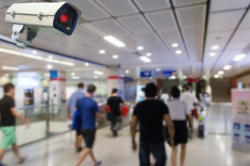 CCTV security indoor camera system operating with blurred image of people walking at train station, transportation, surveillance security, safety technology concept