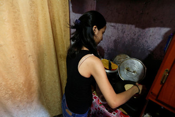 Yennifer Padron cooks arepas in the family room of the house that they share at Petare slum in Caracas