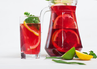 tasty and juicy sangria with citrus in a glass next to the pitcher on a white background.