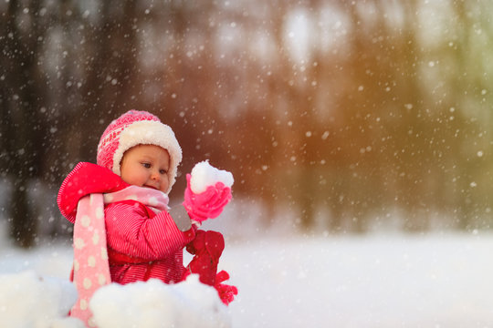 cute little girl play with winter snow